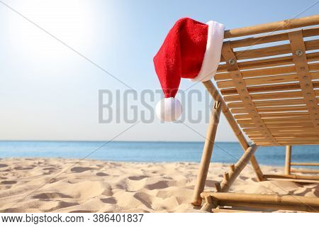 Sun Lounger With Santa's Hat On Beach, Closeup. Christmas Vacation