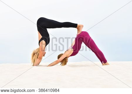 Two Beautiful Young Women Performing Steamy Yoga On The Beach