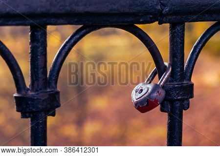 Old Red Heart Shaped Padlock Hanging On The Railing.