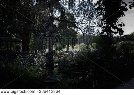 Black Grave Cross In The Cemetery, Dusk Nightfall Night. Gloomy Scary Photo At Dusk, Cemetery Landsc
