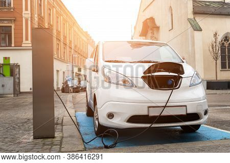 Front View Modern Electric Commercial Van Car Plugged With Fast Charger At Charging Station In Cente