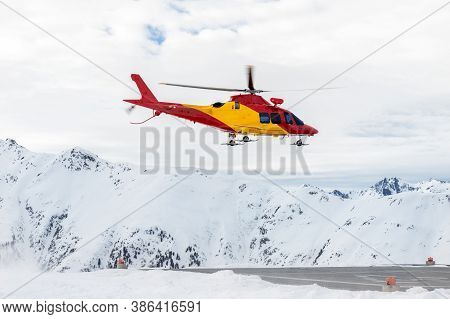 Mountain Ski Life Rescue Medic Helicopter Taking-off From Station Helipad To Search Injured Skiers A