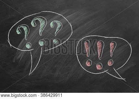 Exclamation Point And Question Mark In Speech Bubbles On Blackboard. Question And Answer. Consultati