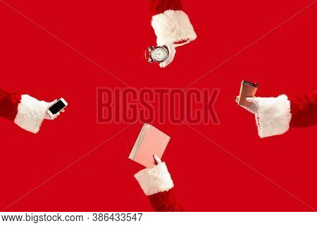 The Hands Of Santa Claus Holding A Gifts On Red Background With Copyspace. New Year, Christmas, Wint