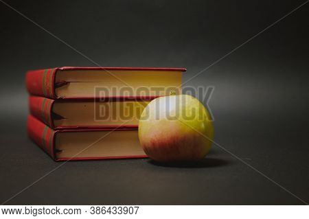 Three Red Books And An Aple On Dark Background. High Quality Photo