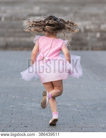 Little Girl In Pink Dress Spinning Around On The Street. Back View