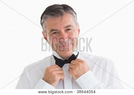 Well-dressed and smiling man adjusting his bow tie in front of camera