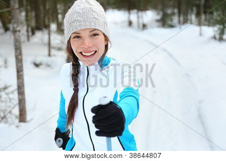 Cross-country skiing woman doing classic nordic cross country skiing in trail tracks in snow covered forest in Quebec, Canada poster