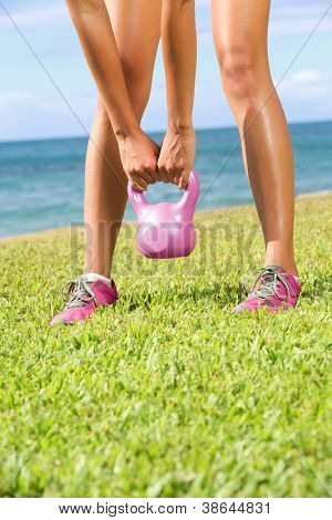 Kettlebell fitness training woman during exercise outside.