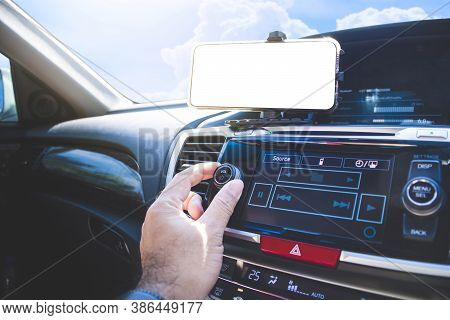 The Driver's Hand Adjust To Volume Button Of Car Audio And A White Blank Display On Smartphone In A