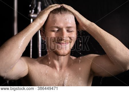 Happy Beautiful Man Standing Under Stream Of Hot Water In Bathroom, Taking Shower, Young Smiling Guy