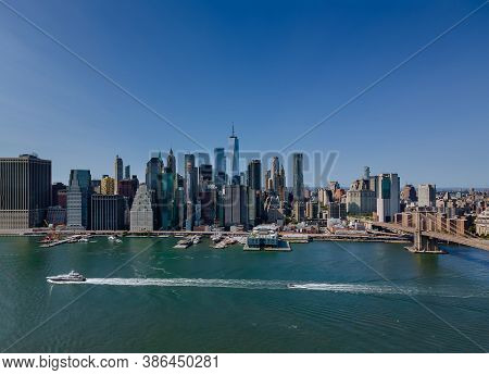 Aerial View Of The Brooklyn Bridge Through The East River To District In Skyline Manhattan America.