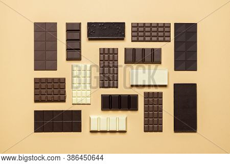 Chocolate Bar Assortment Isolated On A Beige Background. Top View Of Fine Chocolate Collection, Dark