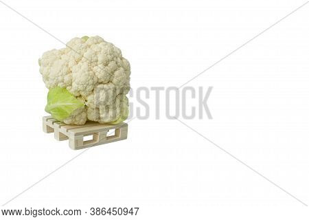 Close Up Of One Fresh Cauliflower On Wooden Mini Pallet Isolated On White Background With Large Copy