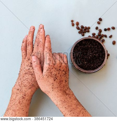 Top View Of Female Hands And A Jar With Roasted Coffee Bean Scrub And Sea Salt On Mint Background In