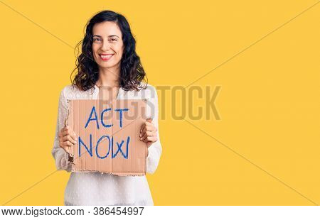 Young beautiful hispanic woman holding act now banner looking positive and happy standing and smiling with a confident smile showing teeth