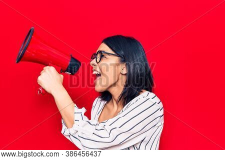 Young beautiful latin woman with angry expression. Screaming loud using megaphone standing over isolated red background