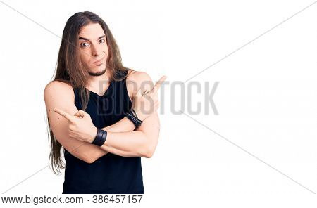 Young adult man with long hair wearing goth style with black clothes pointing to both sides with fingers, different direction disagree