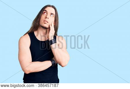 Young adult man with long hair wearing rocker style with black clothes and contact lenses serious face thinking about question with hand on chin, thoughtful about confusing idea