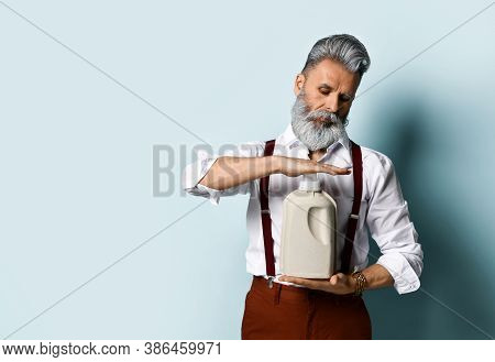 Bearded Man In White Shirt, Brown Pants And Suspenders, Bracelet. Holds A Plastic Paper Eco Bottle,