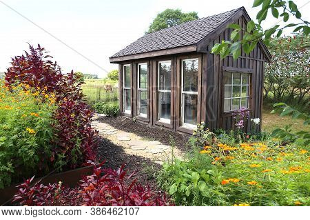 A Rustic Little Wooden Cottage Style Garden Shed Is Surrounded By Beautiful, Colorful Summer Flowers