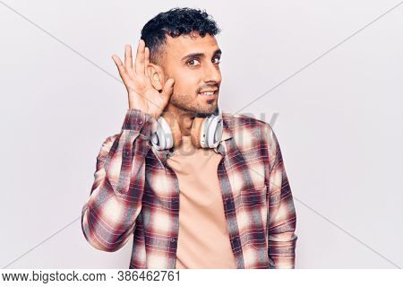Young hispanic man listening to music using headphones smiling with hand over ear listening and hearing to rumor or gossip. deafness concept.