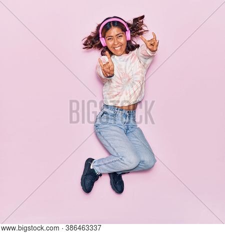 Young beautiful latin woman listening to music using headphones smiling happy. Jumping with smile on face doing rocker sign over isolated pink background