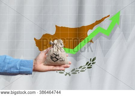 The Concept Of Economic Growth In Republic Of Cyprus. Hand Holds A Bag With Money And An Upward Arro