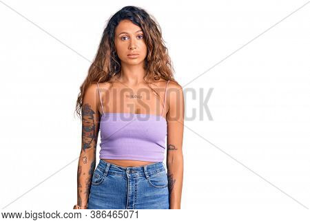 Young hispanic woman with tattoo wearing casual clothes relaxed with serious expression on face. simple and natural looking at the camera.