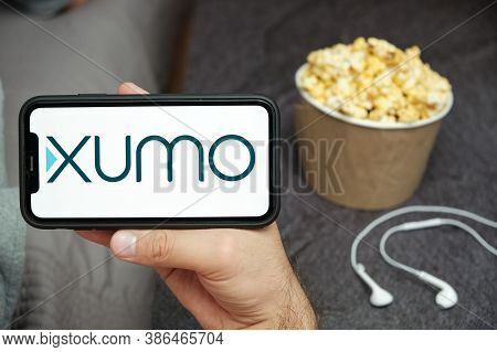 Xumo Logo On The Mobile Phone Screen With Popcorn Box And Apple Earpods On The Background. Leisure T