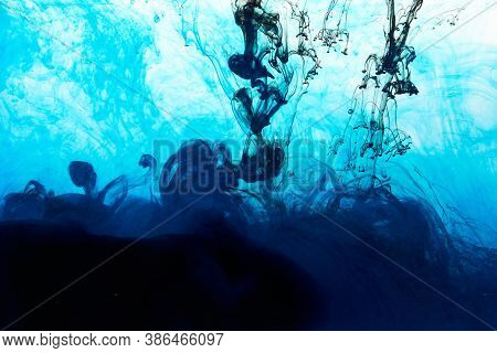Closeup Of A Blue And Black Ink In Water In Motion Isolated On White. Ink Swirling Underwater. Color
