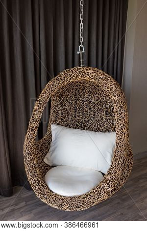Modern Black Rattan Chair Hanging. Hanging Chair In Room Interior. Modern Armchair In Shape Of Eggsh