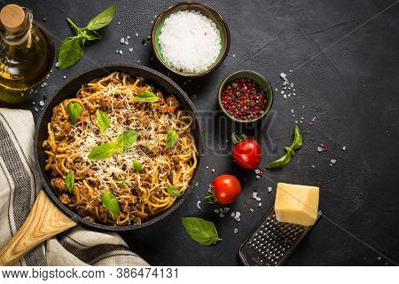 Pasta Bolognese, Meat Ragout In Tomato Sauce In The Skillet At Black Table. Top View With Copy Space