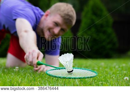 Close Up Badminton Player With Racket In Action. Young Man On Grass Playing Badminton Outdoors. Spor