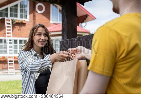 Smiling Beautiful Woman Customer Receiving Order From Delivery Man In Front Of House, Fast Delivery