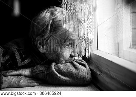 An old woman looking at the window. Black and white photography.