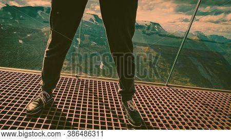 Tourist Feet On Dalsnibba Viewpoint, Geiranger Skywalk Platform Metal Floor Surface And View On Moun