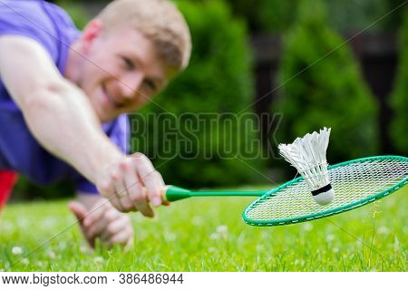 Young Smiling Strong Sport Man Playing Badminton With Racquet And Shuttlecock. Fit Male Athlete Badm