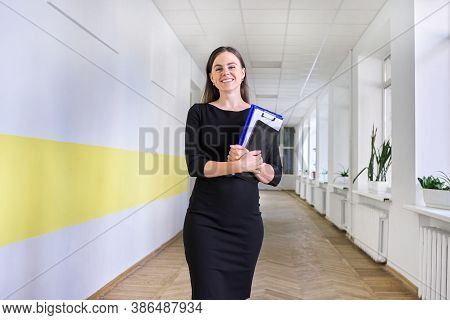 Portrait Of Young Smiling Female Teacher At School. Female In Black Dress With Folder, Digital Table
