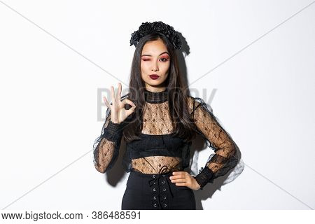 Sassy Beautiful Asian Woman In Witch Costume Showing Okay Gesture, All Under Control. Confident Girl