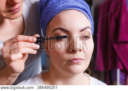 Visage Concept. Close Up Woman Wearing Towel On Wet Hair Getting Make Up On Eyelids. Applying Mascar
