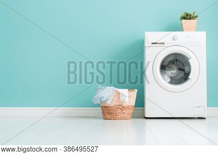 Interior of laundry room with a washing machine on bright teal wall background.