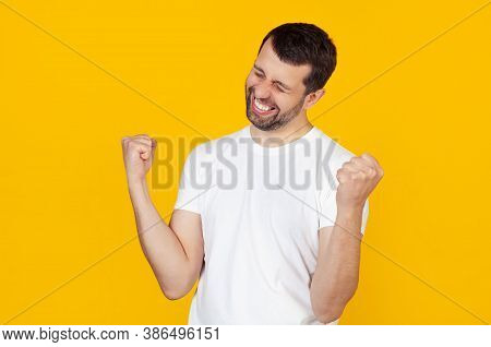 A Young Man With A Beard In A White T-shirt Is Very Happy And Excited, Making A Winner Gesture With