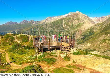 Eggishorn, Switzerland - August 7, 2020: Tourists At Viewing Platform Looking Alpine Glacier. Aletsc