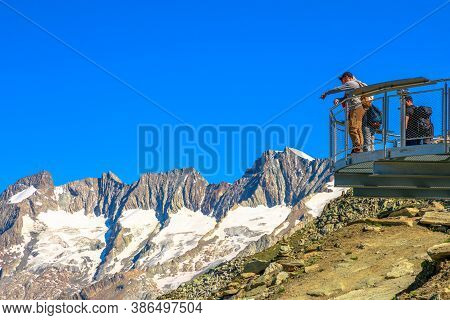Eggishorn, Canton Of Valais, Switzerland - August 6, 2020: Tourists Hikers On Viewing Platform Looki