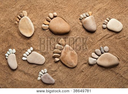 trace bare feet walking made of pebble stones on the beach sand background