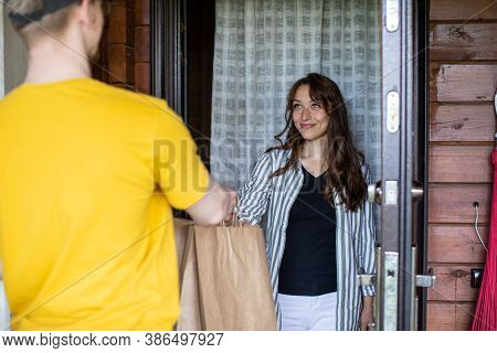 Delivery Man In Yellow Uniform Handing Paper Bags To Recipient, Beautiful Young Woman Customer Recei