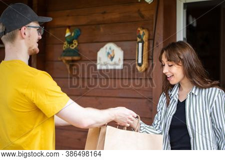 Happy Beautiful Woman Customer Receiving Order From Delivery Man At Home, Courier In Yellow Uniform