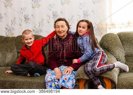 Closeup Portrait Of Happy Great-grandmother With Great-grandchildren On The Sofa At Home