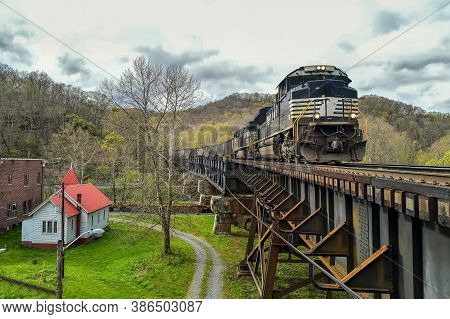 Train Traveling Near A House, An Express Train Traveling Through A Humid Village On A Sunny Summer D